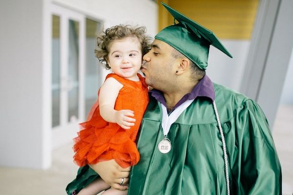 Luis Tolentino in graduation gown, holding a toddler. Credit: Goodwill Excel Center Central And Southern Indiana