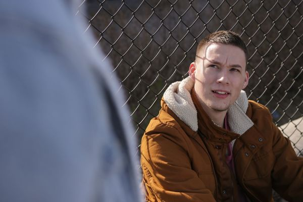 Young man sitting in front of a chain link fence