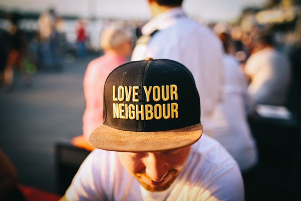 "Man wearing hat that says ""Love your neighbor"""